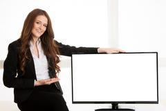 在电视屏幕显示附近的美丽的年轻女商人与另外的文本或图表的拷贝空间 免版税库存照片