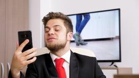 在电视电话会议电话的商人通过他的电话 影视素材