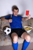 年轻在电视的人观看的橄榄球在家 免版税图库摄影