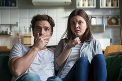 在电视的害怕的千福年的夫妇观看的恐怖片在家 免版税库存照片