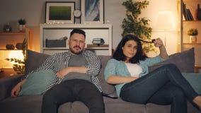 在电视的年轻有家室的人和妇女观看的乏味的电影在家坐长沙发 股票录像