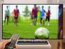 在电视的手表年轻足球队员比赛 免版税库存照片