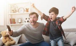 在电视的父亲和儿子观看的橄榄球在家 免版税库存图片