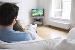 在电视的父亲和女儿观看的动画片 免版税图库摄影