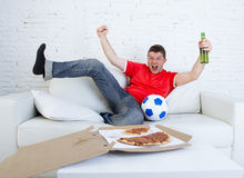 年轻在电视的足球迷人观看的比赛在庆祝目标疯狂愉快在长沙发的队球衣 图库摄影