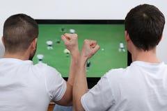 在电视的青年人观看的橄榄球 库存照片