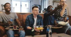 在电视的非裔美国人的男性朋友手表体育 多种族万人迷爱好者被集中和严肃在长沙发用玉米花 库存图片
