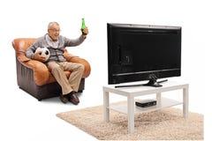在电视的兴奋的成熟人观看的橄榄球 免版税库存照片