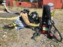 在电话以后的消防队员齿轮 免版税图库摄影