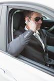在电话佩带的太阳镜的商人 免版税图库摄影