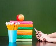 在电话使用的手在书和绿色黑板附近 文本的样品 免版税库存照片