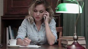 在电话和制造笔记的被集中的少妇谈的事务在她的书桌 影视素材
