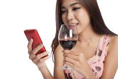 在电话和饮料红葡萄酒的美好的亚洲妇女闲谈 图库摄影