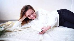在电话在网上读新闻并且高兴看得见逗人喜爱的女孩的画象,说谎在格子花呢披肩的地板上在舒适屋子里与 股票视频