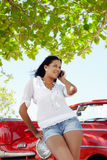 在电话妇女附近的美丽的敞蓬车汽车 免版税库存照片