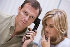 在电话接受的坏夫妇新闻 库存照片