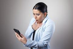 在电话的一则消息冲击的妇女 图库摄影