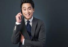 在电话的友好亚洲生意人 库存照片