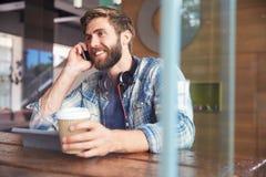 在电话的商人使用在咖啡店的数字式片剂 库存图片