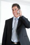在电话的商人在工作场所 图库摄影