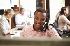 在电话的商人在有会议的书桌在背景中 库存照片