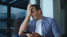 在电话的商人恶化的新闻 沮丧的男性读书冲击了消息 股票录像