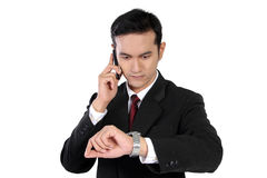 在电话的商人检查时间的,隔绝在白色 免版税库存图片