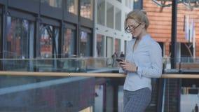在电话的女商人键入的正文消息 免版税库存照片