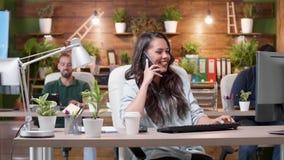 在电话的妇女谈话在一个繁忙的舒适办公室 股票视频