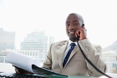在电话的微笑的商人,当读文件时 免版税库存图片