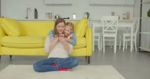在电话的快乐的妈咪和女儿观看的动画片 影视素材