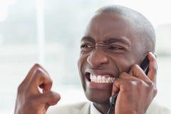 在电话的恼怒的商人 库存照片