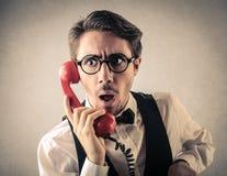 在电话的惊奇的商人 库存照片