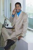 在电话的愉快的商人 图库摄影