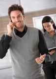 在电话的愉快的生意人 免版税库存照片