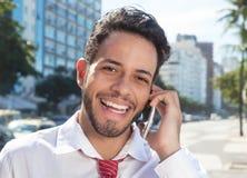 在电话的成功的拉丁商人在城市 免版税库存照片