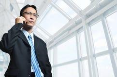 在电话的成熟亚洲生意人 免版税库存图片