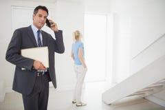 在电话的房地产开发商与被弄脏的妇女在背景中 免版税库存图片