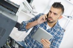 在电话的技术员寻找的帮助,当修理打印机时 免版税图库摄影