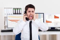 在电话的担心的股票经纪人 库存照片