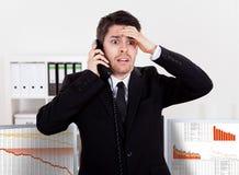 在电话的担心的股票经纪人 免版税图库摄影