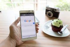 在电话的查寻谷歌在咖啡店 免版税库存照片