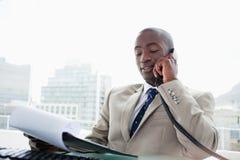 在电话的生意人,当读文件时 免版税库存照片