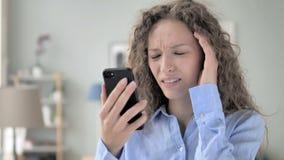 在电话的结果冲击的卷发妇女