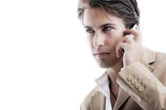 在电话的老练年轻商人 图库摄影