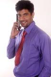 在电话的年轻商人微笑对照相机的 库存照片