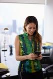 在电话的年轻拉提纳妇女正文消息在办公室 库存照片