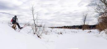 在电话的滑雪者谈话和放松在一次长的远足以后的长凳 全景 图库摄影