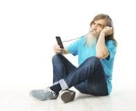 在电话耳机的老人听的音乐 老人胡子 免版税图库摄影