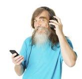 在电话耳机的老人听的音乐 老人胡子 免版税库存图片
